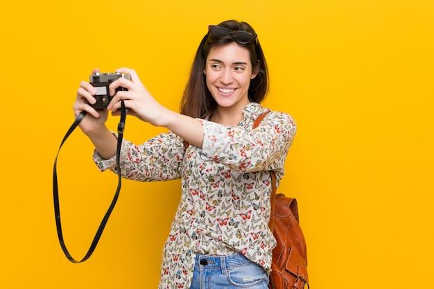 Jovem mulher caucasiana, segurando uma câmera vintage