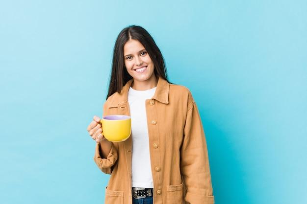 Jovem mulher caucasiana segurando uma caneca de café feliz, sorridente e alegre.