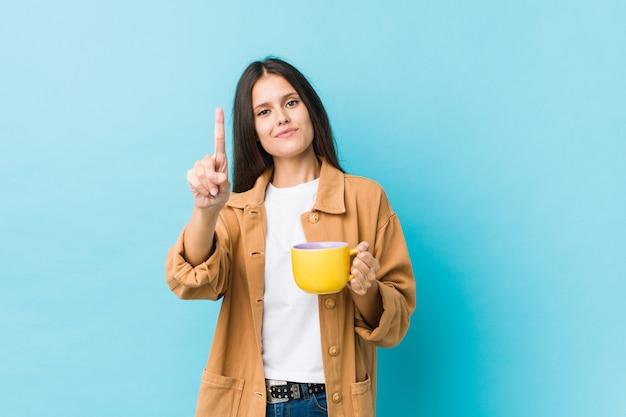 Jovem mulher caucasiana, segurando uma caneca de café, mostrando o número um com o dedo.