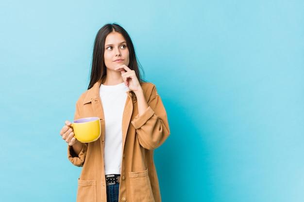 Jovem mulher caucasiana, segurando uma caneca de café, olhando de soslaio com expressão duvidosa e cética.