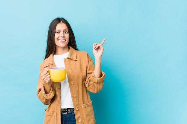 Jovem mulher caucasiana, segurando uma caneca de café sorrindo alegremente apontando com o dedo indicador.