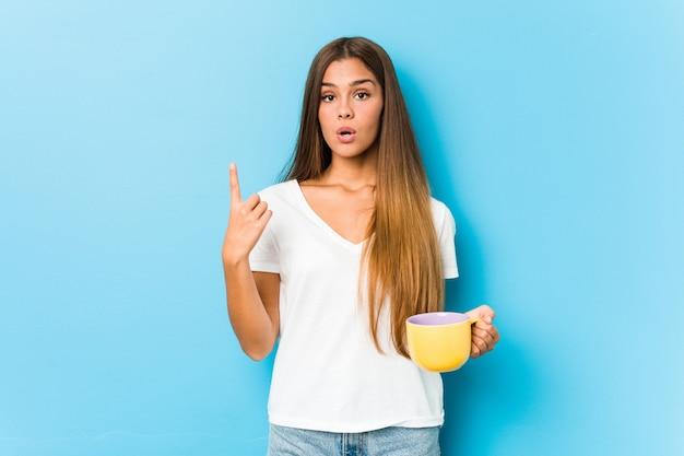 Jovem mulher caucasiana, segurando uma caneca de café, tendo uma ótima idéia