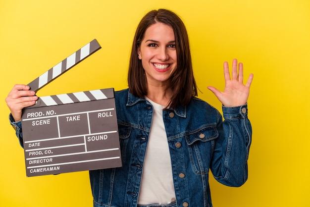 Jovem mulher caucasiana segurando uma claquete isolada em fundo amarelo, sorrindo alegre mostrando o número cinco com os dedos.
