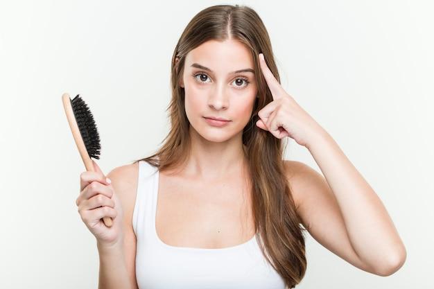 Jovem mulher caucasiana, segurando uma escova de cabelo, apontando seu templo com o dedo, pensando, focado em uma tarefa.
