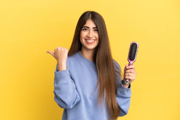 Jovem mulher caucasiana segurando uma escova de cabelo isolada em um fundo azul apontando para o lado para apresentar um produto