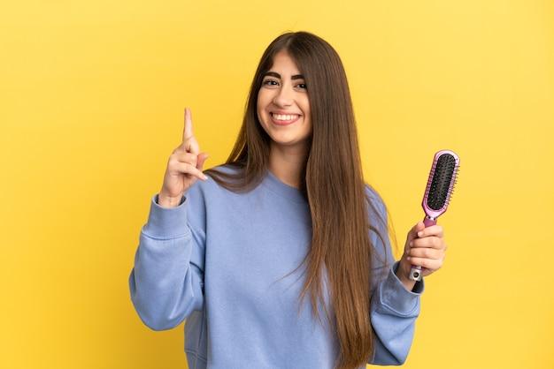 Jovem mulher caucasiana segurando uma escova de cabelo isolada em um fundo azul, mostrando e levantando um dedo em sinal dos melhores