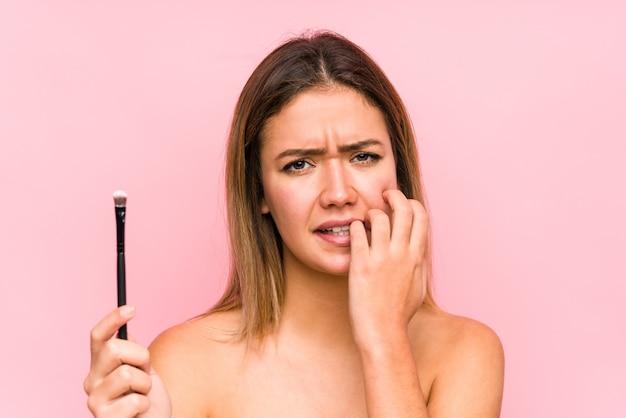 Jovem mulher caucasiana, segurando uma escova de olhos isolada, roer as unhas, nervosa e muito ansiosa.