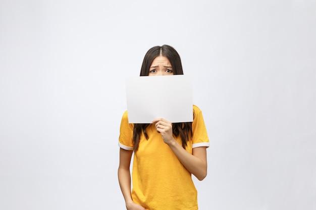 Jovem mulher caucasiana segurando uma folha de papel em branco