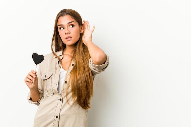 Jovem mulher caucasiana, segurando uma forma de coração, tentando ouvir uma fofoca.