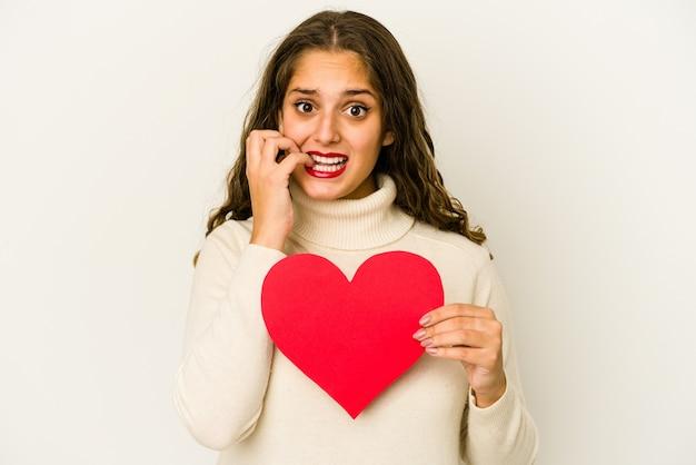 Jovem mulher caucasiana, segurando uma forma de dia dos namorados coração isolada unhas roendo, nervosa e muito ansiosa.