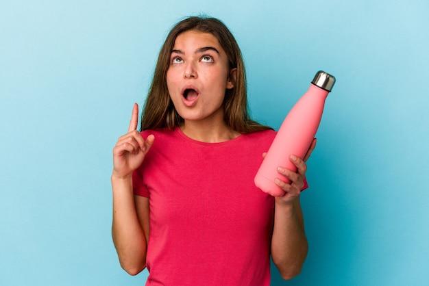Jovem mulher caucasiana segurando uma garrafa de água isolada em um fundo azul apontando para cima com a boca aberta.