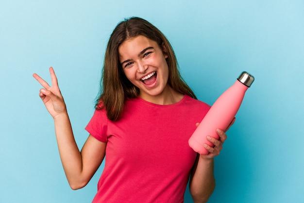 Jovem mulher caucasiana, segurando uma garrafa de água isolada no fundo azul, alegre e despreocupada, mostrando um símbolo de paz com os dedos.