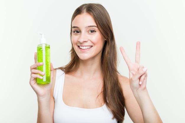Jovem mulher caucasiana, segurando uma garrafa de aloe vera, mostrando o número dois com os dedos.