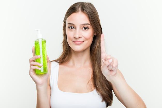 Jovem mulher caucasiana, segurando uma garrafa de aloe vera, mostrando o número um com o dedo.