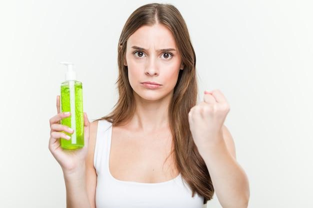 Jovem mulher caucasiana, segurando uma garrafa de aloe vera, mostrando o punho para a câmera, expressão facial agressiva.