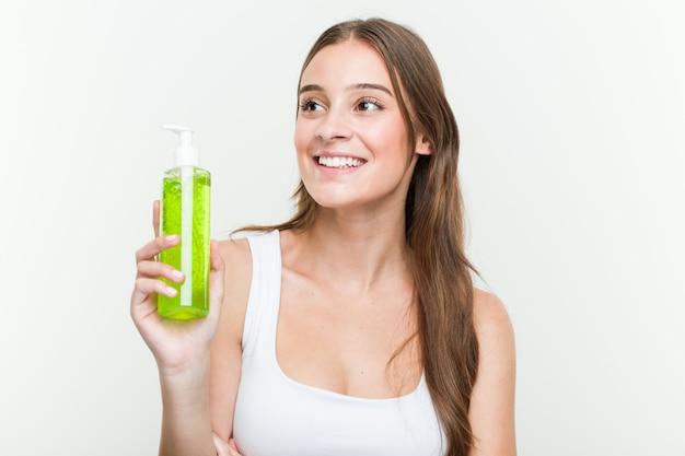 Jovem mulher caucasiana segurando uma garrafa de aloe vera sorrindo confiante com braços cruzados.