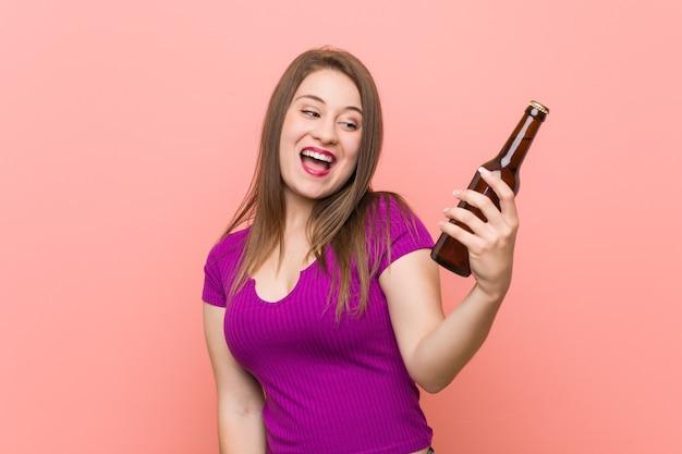 Jovem mulher caucasiana segurando uma garrafa de cerveja