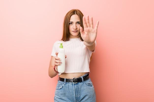 Jovem mulher caucasiana, segurando uma garrafa de creme em pé com a mão estendida, mostrando o sinal de stop, impedindo-o.