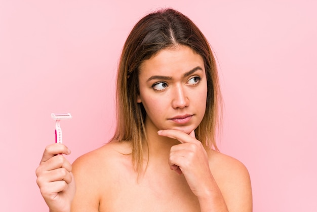 Jovem mulher caucasiana, segurando uma lâmina de barbear isolada jovem mulher caucasiana, segurando uma escova de cabelo isolada, olhando de soslaio com expressão duvidosa e cética. <mixto>