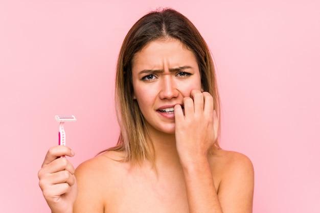 Jovem mulher caucasiana segurando uma lâmina de barbear isolada jovem mulher caucasiana segurando uma escova de cabelo isolada roer unhas, nervosa e muito ansiosa. <mixto>