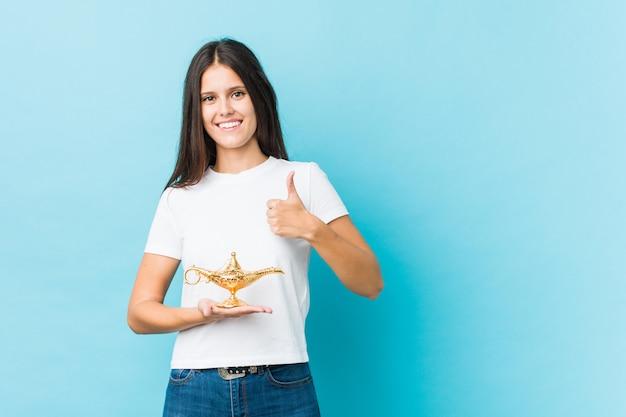 Jovem mulher caucasiana, segurando uma lâmpada mágica, sorrindo e levantando o polegar