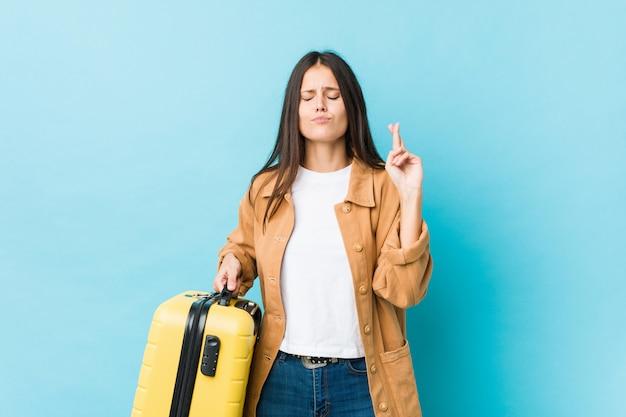 Jovem mulher caucasiana, segurando uma mala cruzando os dedos por ter sorte