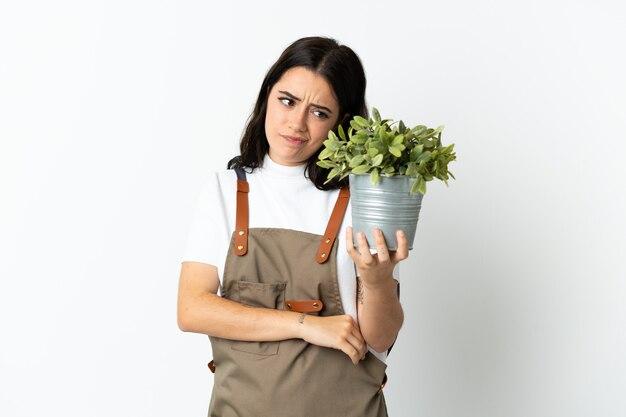 Jovem mulher caucasiana segurando uma planta isolada