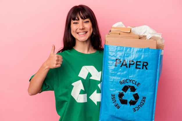 Jovem mulher caucasiana segurando uma sacola de papelão reciclada isolada em um fundo rosa, sorrindo e levantando o polegar