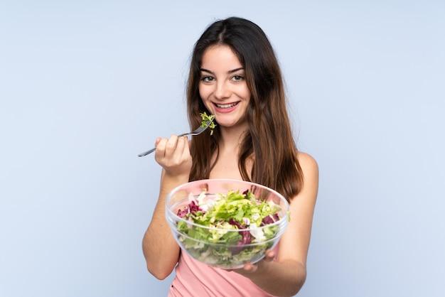 Jovem mulher caucasiana, segurando uma salada isolada na parede azul