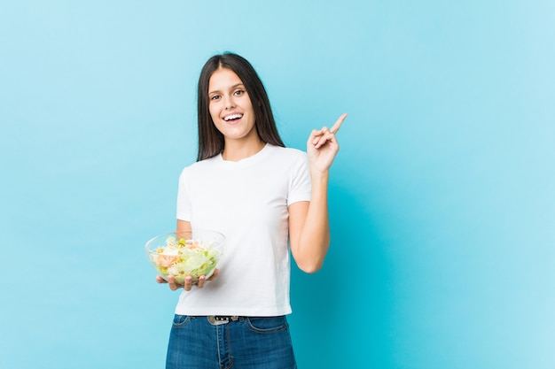 Jovem mulher caucasiana segurando uma salada sorrindo alegremente, apontando com o dedo indicador afastado.