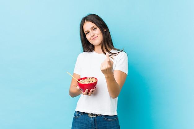 Jovem mulher caucasiana segurando uma tigela de cereais, apontando com o dedo para você, como se fosse um convite para se aproximar.