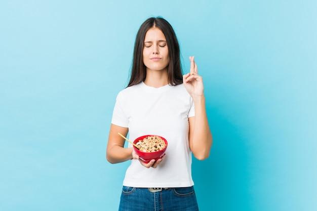 Jovem mulher caucasiana, segurando uma tigela de cereais, cruzando os dedos por ter sorte