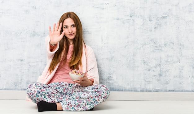 Jovem mulher caucasiana, segurando uma tigela de cereais em pé com a mão estendida, mostrando o sinal de stop, impedindo-o.