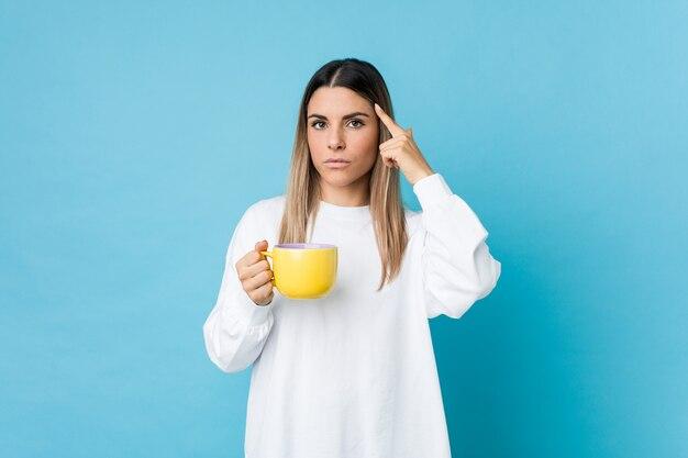 Jovem mulher caucasiana, segurando uma xícara de café, apontando seu templo com o dedo, pensando, focado em uma tarefa.