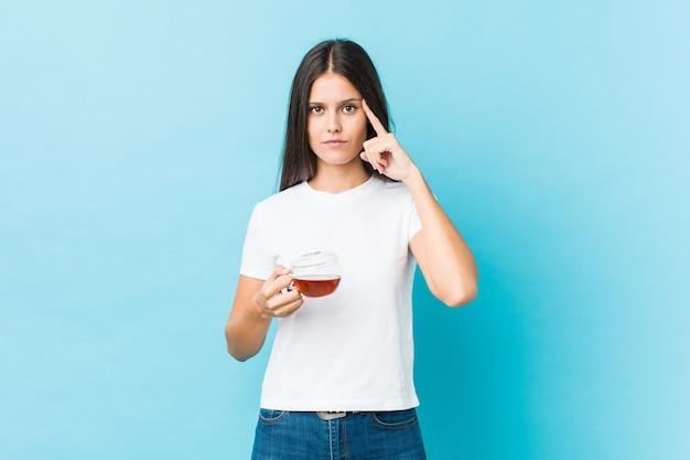 Jovem mulher caucasiana segurando uma xícara de chá, apontando sua têmpora com o dedo, pensando, focada em uma tarefa.