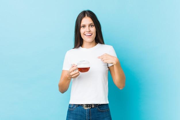Jovem mulher caucasiana, segurando uma xícara de chá surpreendeu apontando para si mesmo, sorrindo amplamente.