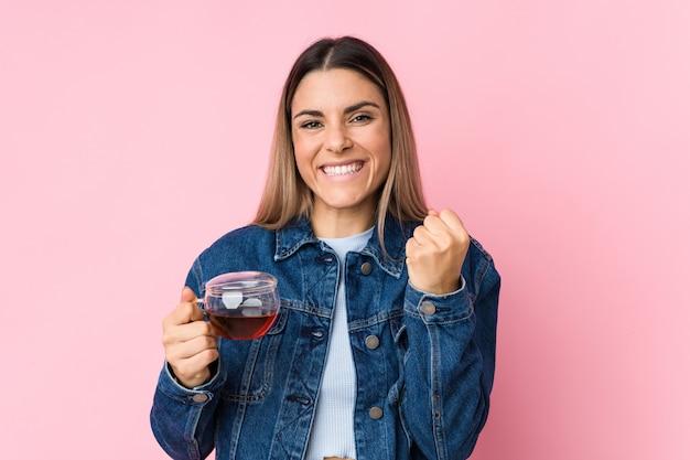 Jovem mulher caucasiana, segurando uma xícara de chá torcendo despreocupada e animada. conceito de vitória