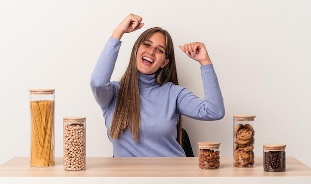 Jovem mulher caucasiana, sentada à mesa com a panela de comida isolada no fundo branco, comemorando um dia especial, pula e levanta os braços com energia.