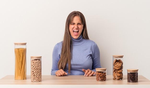 Jovem mulher caucasiana, sentada à mesa com a panela de comida isolada no fundo branco, gritando muito zangada e agressiva.