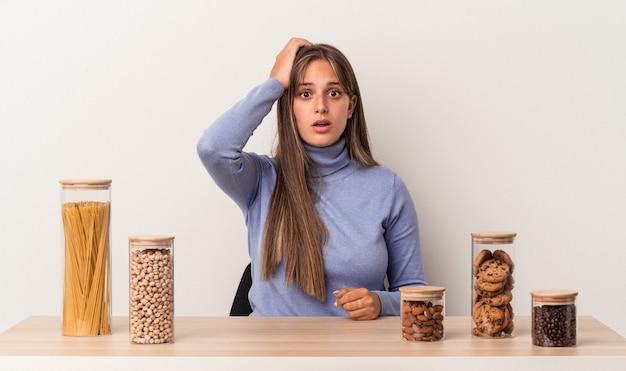 Jovem mulher caucasiana, sentada à mesa com a panela de comida isolada no fundo branco, sendo chocada, ela se lembrou de uma reunião importante.