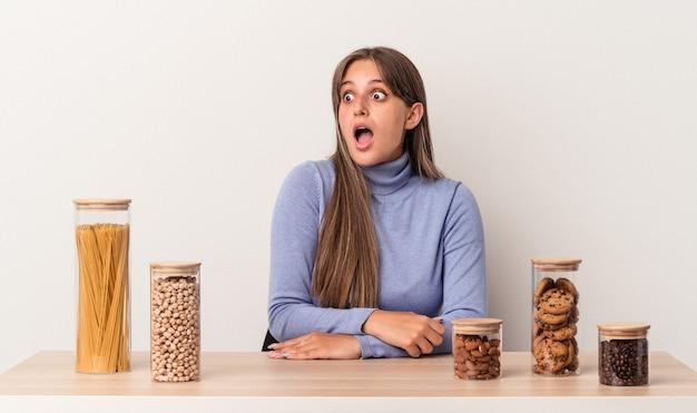 Jovem mulher caucasiana, sentada à mesa com o pote de comida, isolada no fundo branco, sendo chocada por causa de algo que ela viu.