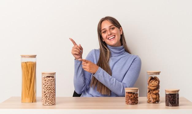 Jovem mulher caucasiana, sentada à mesa com o pote de comida isolado no fundo branco animado, apontando com os indicadores de distância.