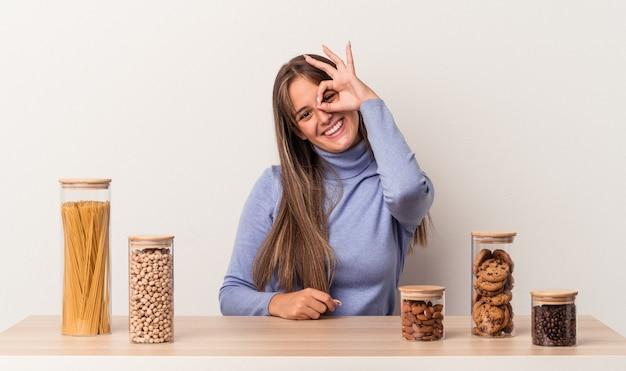 Jovem mulher caucasiana, sentada à mesa com o pote de comida, isolado no fundo branco, animado, mantendo o gesto ok no olho.