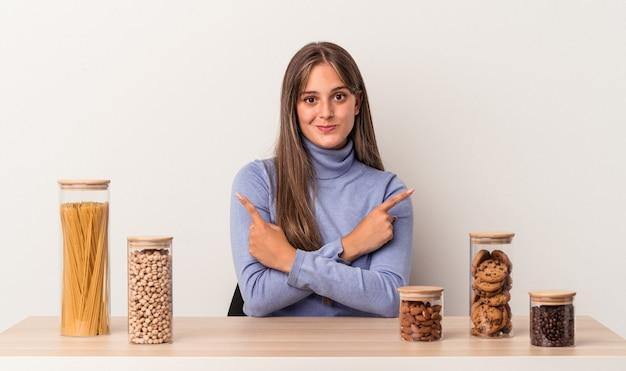 Jovem mulher caucasiana, sentada à mesa com o pote de comida isolado no fundo branco aponta para o lado, está tentando escolher entre duas opções.