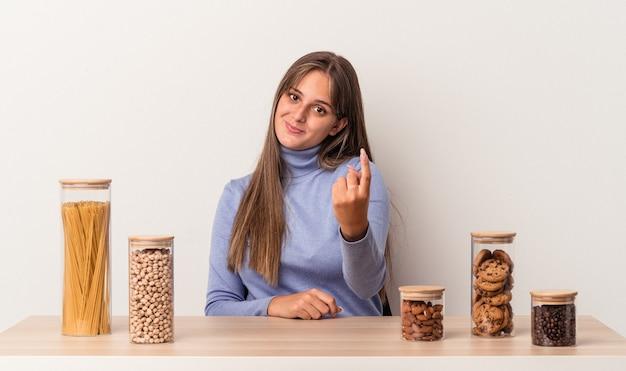 Jovem mulher caucasiana, sentada à mesa com o pote de comida isolado no fundo branco, apontando com o dedo para você como se fosse um convite para se aproximar.