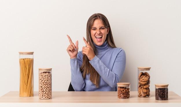 Jovem mulher caucasiana sentada à mesa com o pote de comida isolado no fundo branco, apontando com os indicadores para um espaço de cópia, expressando entusiasmo e desejo.