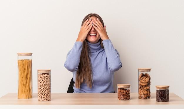 Jovem mulher caucasiana, sentada à mesa com o pote de comida isolado no fundo branco, cobre os olhos com as mãos, sorri amplamente à espera de uma surpresa.
