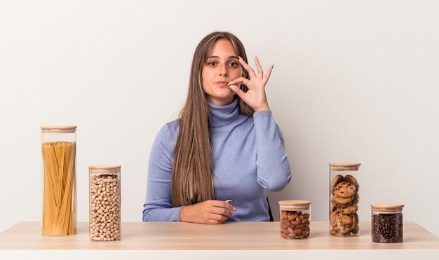 Jovem mulher caucasiana, sentada à mesa com o pote de comida, isolado no fundo branco com os dedos nos lábios, mantendo um segredo.