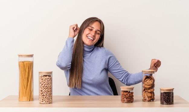 Jovem mulher caucasiana, sentada à mesa com o pote de comida, isolado no fundo branco, dançando e se divertindo.