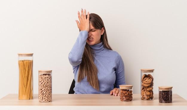Jovem mulher caucasiana, sentada à mesa com o pote de comida isolado no fundo branco, esquecendo de algo, batendo na testa com a palma da mão e fechando os olhos.
